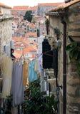 Uma mulher que pendura a lavanderia em uma linha entre duas casas fotografia de stock royalty free