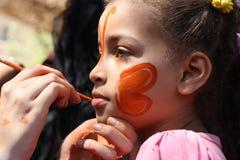 Uma mulher que pinta uma face dos meninos no evento da caridade Fotografia de Stock