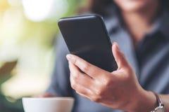 Uma mulher que realiza e que usa o telefone celular com o copo de café na tabela de madeira no café fotos de stock royalty free