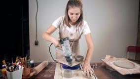 Uma mulher que seca seus produtos da argila video estoque
