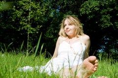 Uma mulher que senta-se em um campo Imagem de Stock Royalty Free
