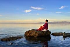 Uma mulher que senta-se na opinião do lago Fotos de Stock Royalty Free