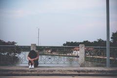 Uma mulher que senta-se na ponte com sentimento triste fotos de stock