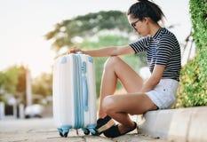 Uma mulher que senta-se na rua com sua mala de viagem azul pronta ao tr foto de stock