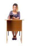 Uma mulher que senta-se na tabela e que trabalha em uma tabuleta Foto de Stock Royalty Free