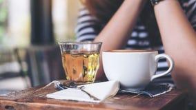 Uma mulher que senta-se no café com os copos do café e do chá quentes na tabela de madeira do vintage Fotos de Stock Royalty Free