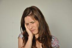 Uma mulher que sofre da dor de cabeça Fotos de Stock