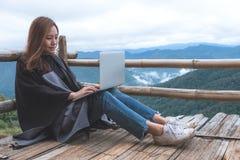 Uma mulher que trabalha e que datilografa no portátil ao sentar-se no balcão de madeira com as montanhas verdes no dia nevoento c fotografia de stock royalty free