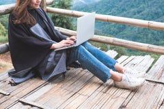 Uma mulher que trabalha e que datilografa no portátil ao sentar-se no balcão de madeira com as montanhas verdes no dia nevoento c foto de stock royalty free