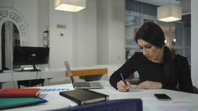 Uma mulher que trabalha no computador, tomando notas em uma folha, amarrota-se e lances vídeos de arquivo