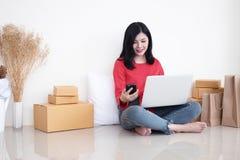 Uma mulher que usa o smartphone e o portátil Está olhando na vista superior e no sorriso imagem de stock