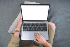 Uma mulher que usa-se e tocando no touchpad do portátil com a tela branca vazia ao sentar-se na sala de visitas imagens de stock