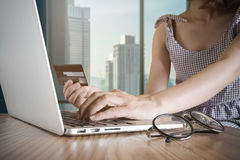 Uma mulher que usa seu cartão de crédito com seu portátil para em linha shoping Imagens de Stock