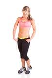 Uma mulher que usa uma fita métrica medir seu tamanho da cintura Fotos de Stock Royalty Free