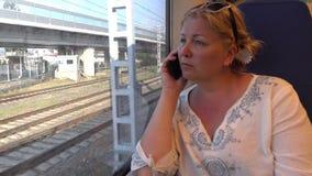 Uma mulher que viaja pelo trem Fala no telefone Imagens de Stock Royalty Free