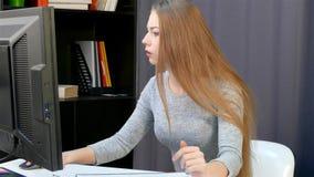Uma mulher reescreve dados de um monitor do computador com uma pena video estoque
