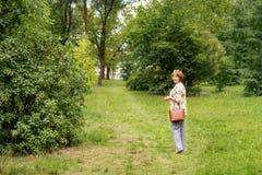 Uma mulher ruivo, de meia idade que anda ao longo do trajeto verde gramíneo no parque e que olha para trás imagem de stock