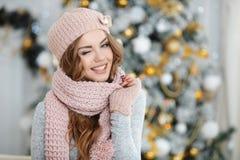 Uma mulher ruivo no chapéu cor-de-rosa perto da árvore de Natal Imagens de Stock