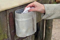 Uma mulher rural idosa joga um guardanapo sujo amarrotado em um sma Imagens de Stock Royalty Free