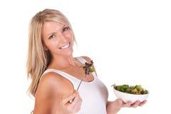 Uma mulher saudável com salada no fundo branco Foto de Stock