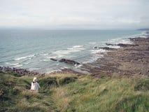 Uma mulher senta-se apenas como as ondas que quebram em rochas da linha costeira Fotografia de Stock Royalty Free