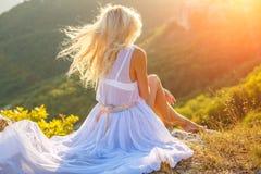 Uma mulher senta-se em uma rocha e olha-se a vista bonita no sol fotografia de stock