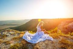 Uma mulher senta-se em uma rocha e olha-se a vista bonita no sol imagem de stock royalty free