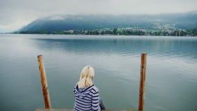 Uma mulher senta-se em um cais de madeira, olha-se as montanhas e o lago da montanha na névoa tiro do steadicam filme