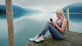 Uma mulher senta-se em um cais de madeira, olha-se as montanhas e o lago da montanha em Áustria Usa um smartphone vídeos de arquivo