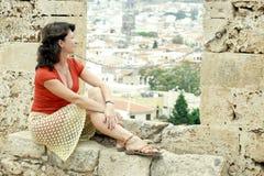 Uma mulher senta-se em uma parede e olha-se na distância Fotos de Stock