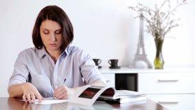 Uma mulher senta-se na tabela e escreve-se algo com um ballpen video estoque