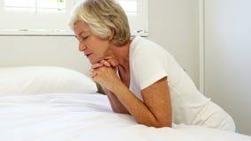 Uma mulher superior está rezando em seu quarto vídeos de arquivo