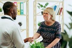 Uma mulher superior que visita um terapeuta na cl?nica fotos de stock royalty free