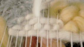 Uma mulher tece em um tear que um bordado bonito fez do fio, em um estúdio home, filme