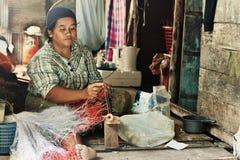 Uma mulher tece uma rede Fotografia de Stock Royalty Free