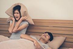 Uma mulher tem um incômodo ao homem que ama dormir ruidosamente ressonando imagens de stock