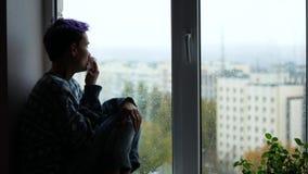 Uma mulher tem um nariz ralo Uma moça senta-se perto de uma janela, ele o ` s que chove fora depression filme