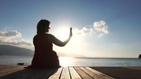 Uma mulher tira fotos de uma linda paisagem marítima no telefone em câmera lenta filme