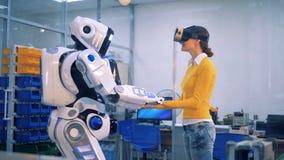 Uma mulher toma as mãos do ` s do robô e olha ao redor video estoque