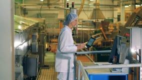 Uma mulher trabalha com um portátil em uma fábrica da produção alimentar filme