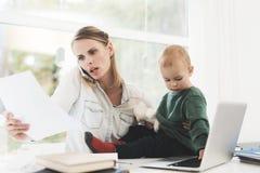 Uma mulher trabalha durante licenças de parto em casa Uma mulher trabalha e importa-se com uma criança ao mesmo tempo Imagem de Stock Royalty Free