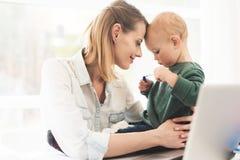 Uma mulher trabalha durante licenças de parto em casa Uma mulher trabalha e importa-se com uma criança ao mesmo tempo Imagem de Stock