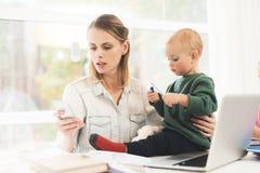Uma mulher trabalha durante licenças de parto em casa Uma mulher trabalha e importa-se com uma criança ao mesmo tempo Fotos de Stock