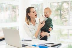 Uma mulher trabalha durante licenças de parto em casa Uma mulher trabalha e importa-se com uma criança ao mesmo tempo Imagens de Stock
