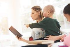 Uma mulher trabalha durante licenças de parto em casa Uma mulher trabalha e importa-se com crianças ao mesmo tempo Imagem de Stock Royalty Free