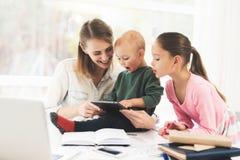 Uma mulher trabalha durante licenças de parto em casa Uma mulher trabalha e importa-se com crianças ao mesmo tempo Fotos de Stock Royalty Free