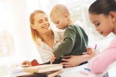 Uma mulher trabalha durante licenças de parto em casa Uma mulher trabalha e importa-se com crianças ao mesmo tempo Imagens de Stock
