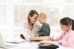 Uma mulher trabalha durante licenças de parto em casa Uma mulher trabalha e importa-se com crianças ao mesmo tempo Foto de Stock Royalty Free