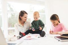 Uma mulher trabalha durante licenças de parto em casa Uma mulher trabalha e importa-se com crianças ao mesmo tempo Fotografia de Stock Royalty Free
