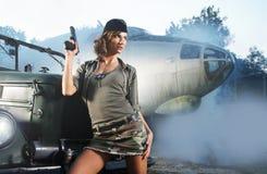 Uma mulher triguenha nova que levanta na roupa militar imagens de stock royalty free